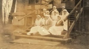 Nurses on the steps of the Naval ward, the Queen Alexandra Hospital, FAU, Dunkirk, 1918. Top row (left to right) - Wilson, Jefferys, Pease. 2nd row - King, Welsh, Borwick. 3rd row - Lawson, Molloy, Springhall