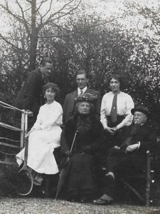 Ernie Grosvenor (centre) with the Evans family, The Lawn, c. 1914. Molly seated on left with tennis racket