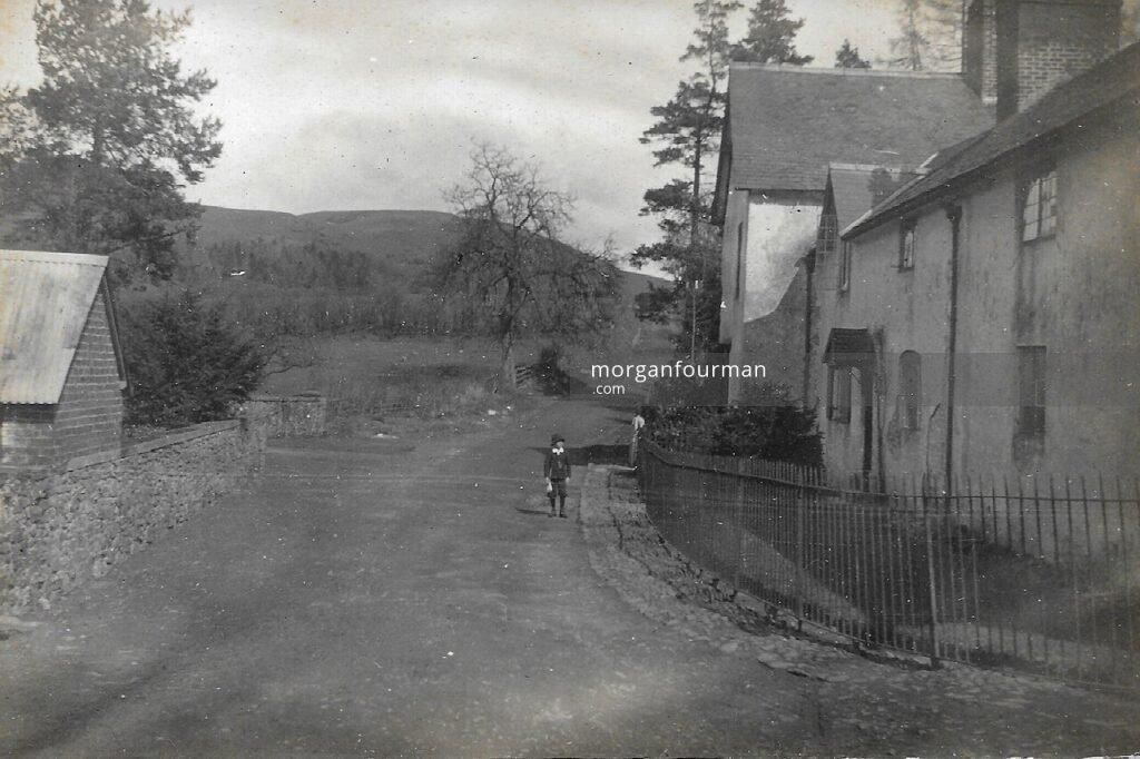 Noel Downing standing outside Ratlinghope Manor House, 1899
